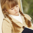 Young Girl Sitting On Wooden Seat Reading Book — Stockfoto