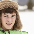 Portrait Of Teenage Boy In Snow Wearing Fur Hat - 图库照片