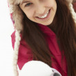 Teenage Girl Holding Snowball Wearing Fur Hat - 图库照片