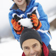 Young Boy About To Drop Snowball On Fathers Head - Stock Photo
