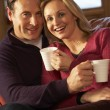 Middle Aged Couple Sitting On Sofa With Hot Drinks — Stock Photo #11891292