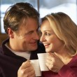 Stock Photo: Middle Aged Couple Sitting On SofWith Hot Drinks