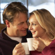 Stock Photo: Middle Aged Couple Sitting On Sofa With Hot Drinks