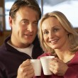 Middle Aged Couple Sitting On Sofa With Hot Drinks — Stock Photo #11891305