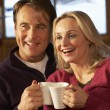 Middle Aged Couple Sitting On Sofa With Hot Drinks Watching TV — Stock Photo