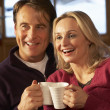 Middle Aged Couple Sitting On Sofa With Hot Drinks Watching TV — Stock Photo #11891310
