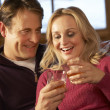 Stock Photo: Middle Aged Couple Sitting On SofWith Glasses Of Whisky