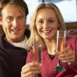Middle Aged Couple Sitting On Sofa With Glasses Of Champagne — Stock Photo