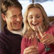 Middle Aged Couple Sitting On Sofa With Glasses Of Champagne — Stock Photo #11891344