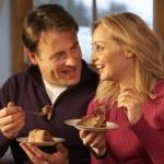Couple Enjoying Slice Of Cake Sitting On Sofa — Stock Photo #11891431
