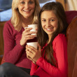 Stock Photo: Portrait Of Mother And Daughter Relaxing On SofTogether With H