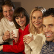 Stock Photo: Group Of Middle Aged Couples Sitting On Sofa With Hot Drinks Tal