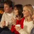 Group Of Middle Aged Couples Sitting On Sofa With Hot Drinks Wat - Stock Photo
