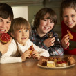 Group Of Children Enjoying Plate Of Cakes In Kitchen — Stock Photo