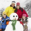 Family Building Snowman On Ski Holiday In Mountains — Stok fotoğraf