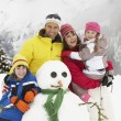 Family Building Snowman On Ski Holiday In Mountains — Stockfoto