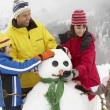 Family Building Snowman On Ski Holiday In Mountains — Stock fotografie