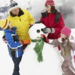 Family Building Snowman On Ski Holiday In Mountains — Foto de Stock