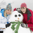 Stock Photo: Two Female Friends Building SnowmOn Ski Holiday In Mountains
