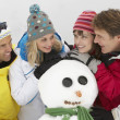 Stock Photo: Group Of Friends Building SnowmOn Ski Holiday In Mountains