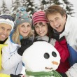 Group Of Friends Building Snowman On Ski Holiday In Mountains — Stock Photo