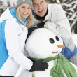 Stock Photo: Middle Aged Couple Building SnowmOn Ski Holiday In Mountains