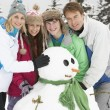Teenage Family Building Snowman On Ski Holiday In Mountains — Stock Photo #11891965