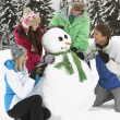 Teenage Family Building Snowman On Ski Holiday In Mountains — Stock fotografie
