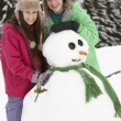 Two Teenagers Building Snowman On Ski Holiday In Mountains — Stock Photo #11891972