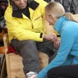 Sales Assistant Helping Man To Try On Ski Boots In Hire Shop - Stock Photo