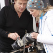 Sales Assistant Helping Advising Female Customer On Ski Boots In - Stock Photo