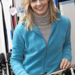 Female Sales Assistant With Skis In Hire Shop — Photo