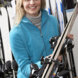 Female Sales Assistant With Skis In Hire Shop — Zdjęcie stockowe