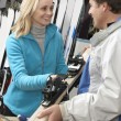 Stock Photo: Female Sales Assistant Handing Skis To Customer In Hire Shop