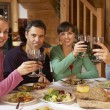 Stock Photo: Group Of Friends Enjoying Meal In Alpine Chalet Together