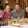 Royalty-Free Stock Photo: Teenage Family Enjoying Meal In Alpine Chalet Together