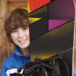 Boy With Snowboard On Ski Holiday In Front Of Wooden Background — Stock fotografie
