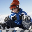 Young Boy Sitting In Snow With Snowboard - Stock Photo