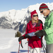 Couple Looking At Map Whilst On Ski Holiday In Mountains - Stock Photo