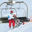 Stock Photo: Mother And Daughter Getting Off chair Lift On Ski Holiday In Mou