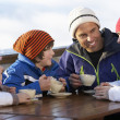 Stock Photo: Family Enjoying Hot Drink In Café At Ski Resort