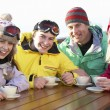 Royalty-Free Stock Photo: Teenage Family Enjoying Hot Drink In Café At Ski Resort