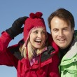 Stock Photo: Couple Standing In Snow Wearing Warm Clothes On Ski Holiday In M