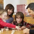 Stock Photo: Family Playing Dominoes In Kitchen