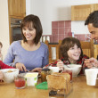 Family Eating Breakfast Together In Kitchen — Stock Photo #11893241