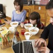 Family Using Gadgets Whilst Eating Breakfast Together In Kitchen — Stok fotoğraf