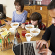Family Using Gadgets Whilst Eating Breakfast Together In Kitchen — Foto de Stock