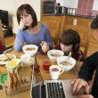 Family Using Gadgets Whilst Eating Breakfast Together In Kitchen - Zdjęcie stockowe