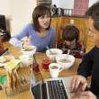 Family Using Gadgets Whilst Eating Breakfast Together In Kitchen — Stock Photo #11893258