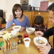 Family Eating Breakfast Together In Kitchen Whilst Children Play — Стоковая фотография